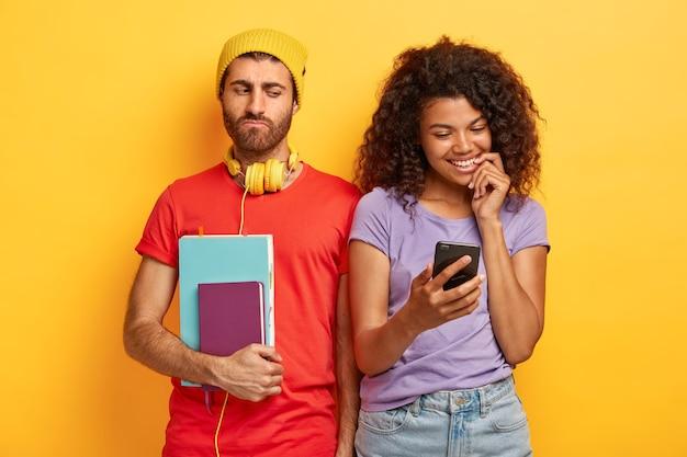 Felice coppia elegante in posa contro il muro giallo con gadget Foto Gratuite