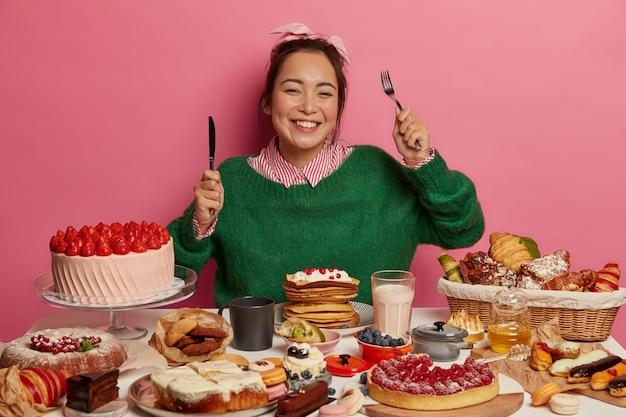 Счастливая женщина держит вилку и нож, имеет хороший аппетит к сладким десертам, имеет зубастую улыбку, наслаждается вкусным блюдом, изолированным за розовой стеной. Бесплатные Фотографии