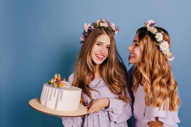 彼女の妹を保持しているケーキを見て花輪のうれしい女性 無料写真