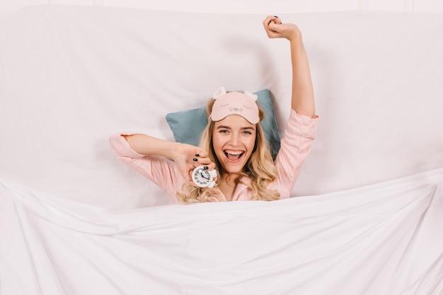 Счастливая женщина в пижаме, растягиваясь в постели Бесплатные Фотографии