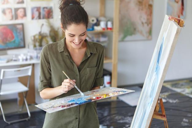 Felice donna che lavora come pittrice, in piedi vicino a cavalletto, con in mano un pennello, creando quadri astratti con oli colorati, con buon umore e ispirazione. disegno femminile su tela. concetto d'arte Foto Gratuite