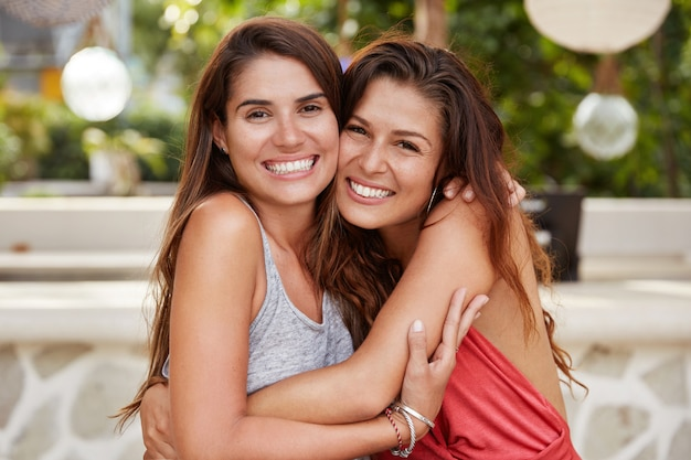 Felice giovani migliori amiche con un sorriso splendente, un aspetto piacevole e attraente, abbracciati e siedono vicini l'uno all'altro Foto Gratuite