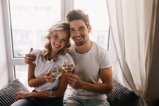 아내와 함께 기념일을 축하하는 기쁜 젊은 남자. 샴페인을 즐기고 웃는 소녀. 무료 사진