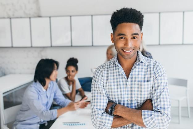 팔을 포즈를 취하는 아프리카 헤어 스타일을 가진 기쁜 젊은 남자가 다른 직원들과 그의 사무실에서 교차했습니다. 직장에서 회의 동안 웃 고 파란색 셔츠에 남성 관리자. 무료 사진