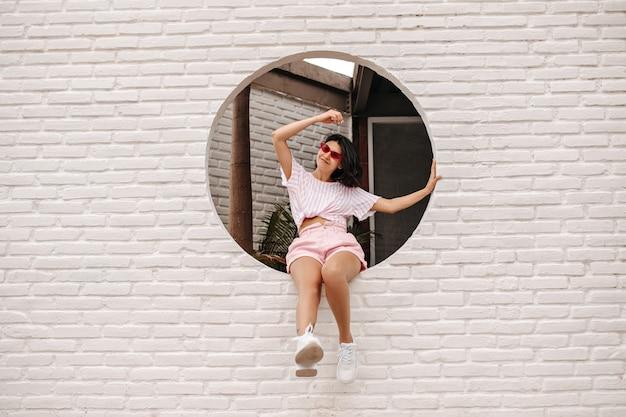 벽돌로 벽에 앉아 좋은 분위기에서 다행 젊은 여자. 미소로 도시 배경에 포즈 행복 갈색 머리 여자의 야외 샷. 무료 사진