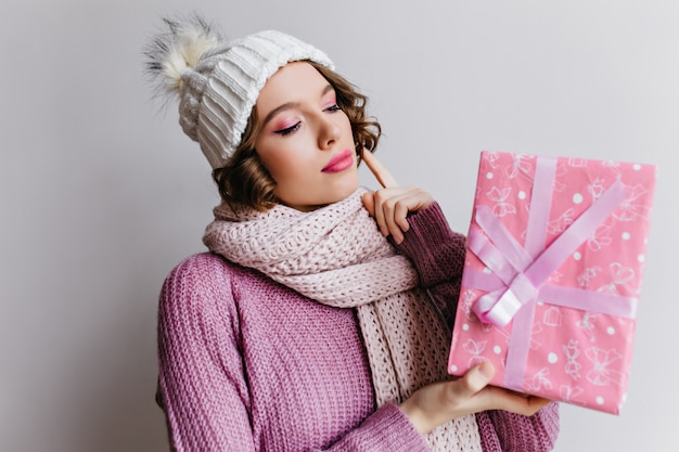 La giovane donna felice indossa il cappello bianco lavorato a maglia che tiene il presente del nuovo anno. meraviglioso modello femminile in posa con scatola regalo rosa decorata con nastro carino. Foto Gratuite