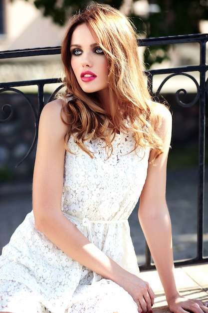 Glamor beauty portrait of beautiful sensual caucasian young woman model with evening makeup in white summer dress posing on the street background Free Photo