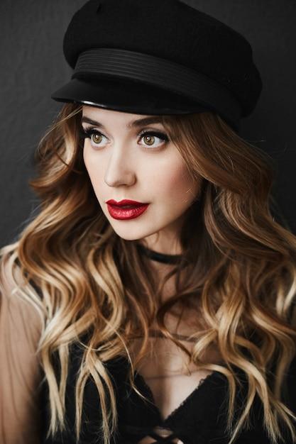 明るい化粧と完全なセクシーな唇、黒い帽子と暗い背景でポーズスタイリッシュな黒いランジェリーで美しくセクシーな金髪モデルの女の子の華やかでファッショナブルな肖像画 Premium写真