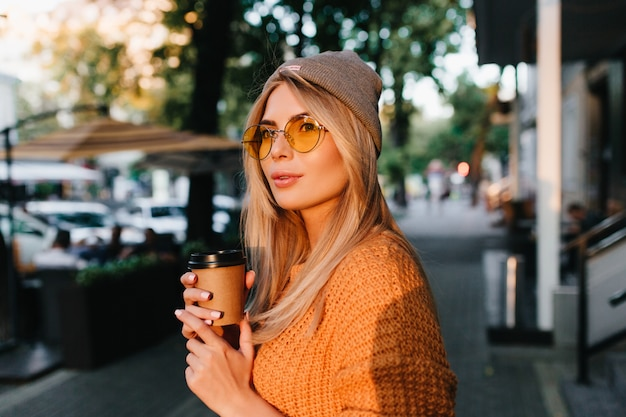 Affascinante donna bionda in occhiali da sole rotondi che trasportano tazza di caffè e distoglie lo sguardo davanti alla strada ombreggiata Foto Gratuite