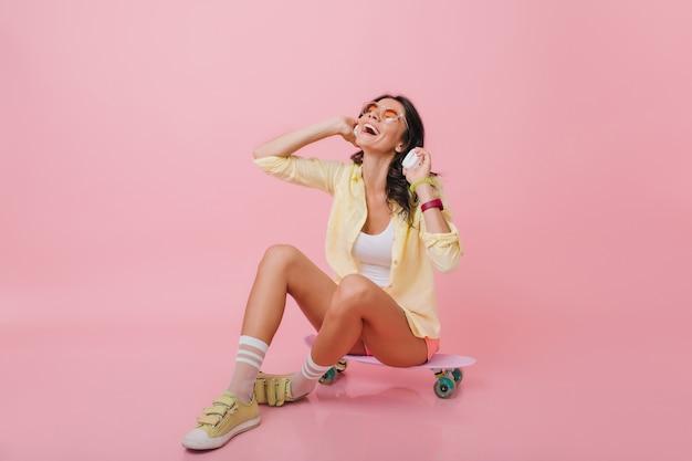 足を組んでロングボードに座っている日焼けした肌を持つ魅力的なブルネットの少女。ヘッドフォンで音楽を聴いている黄色いスニーカーでロマンチックなヒスパニック系女性の屋内の肖像画。 無料写真