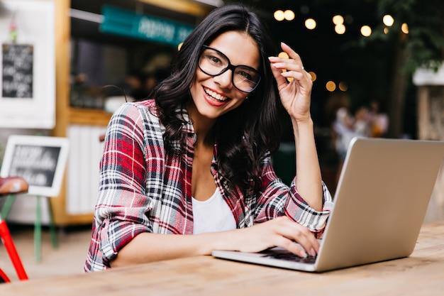 Гламурная женщина-фрилансер, наслаждаясь утром и работающая с ноутбуком. фото веселой латинской дамы в клетчатой рубашке, позирующей в очках. Бесплатные Фотографии