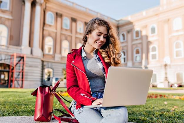 コンピューターで大学の前の庭に座っている赤いジャケットの魅力的な女子学生 無料写真