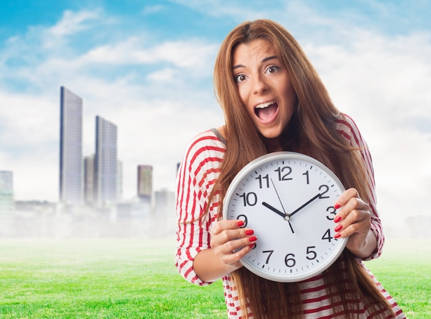 Glamorous girl in harry with big clock. Free Photo