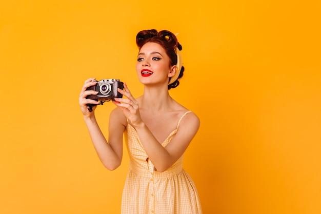 사진을 찍는 매력적인 핀 업 소녀. 노란색 공간에 카메라 서 영감 된 생강 여자. 무료 사진