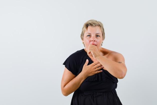 검은 블라우스에 기침하고 불편 해 보이는 매력적인 여자 무료 사진