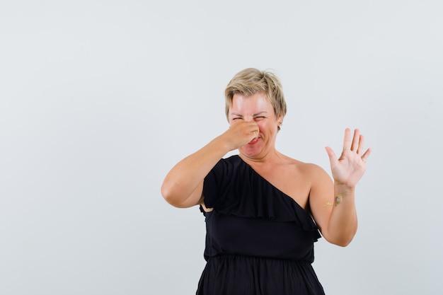 거부하는 방식으로 손을 들고 불편한 표정을 짓는 동안 그녀의 코를 꼬집는 검은 블라우스에 매력적인 여자 무료 사진