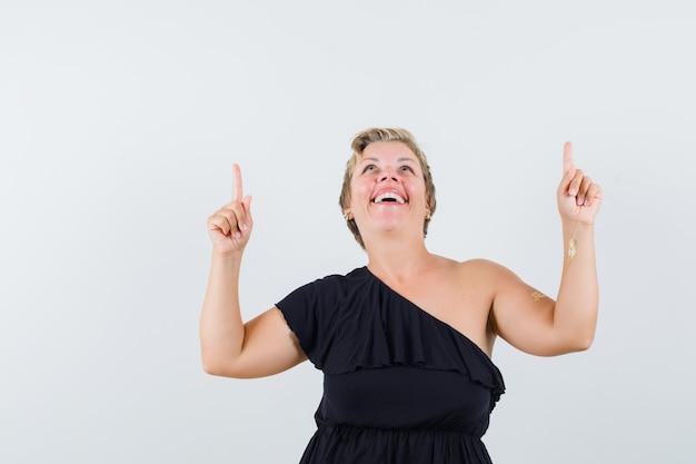 웃으면 서 기분 좋은 찾고있는 동안 가리키는 검은 블라우스에 매력적인 여자 무료 사진