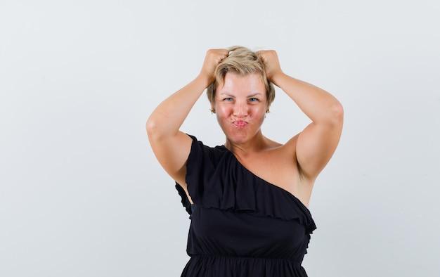 검은 블라우스에 매력적인 여자가 머리에 손을 대고 입술을 삐죽이고 자신감을 찾는 동안 무료 사진