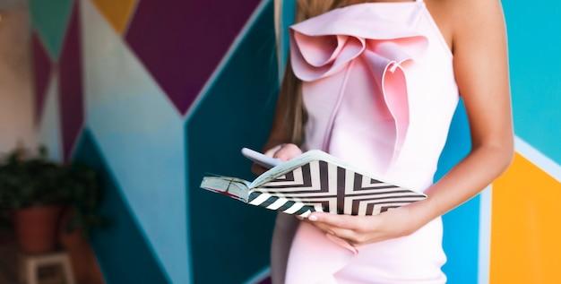 ノートブックとスマートフォンを保持しているエレガントなピンクのドレスの魅力的な女性 無料写真