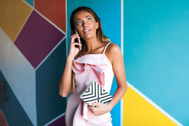 電話で話しているエレガントなピンクのドレスの魅力的な女性 無料写真