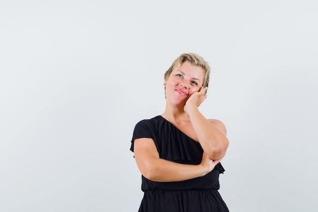 검은 블라우스에 그녀의 뺨에 손을 잡고 밝게 보이는 동안 포즈를 취하는 매력적인 여자. 전면보기. 무료 사진