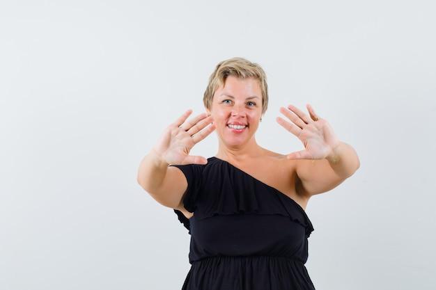 검은 블라우스에 그녀의 열린 손바닥을 보여주는 자신감을 찾고 매력적인 여자 무료 사진