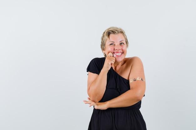 검은 블라우스에 그녀의 뺨에 손을 잡고 메리를 찾고있는 동안 웃 고 매력적인 여자 무료 사진