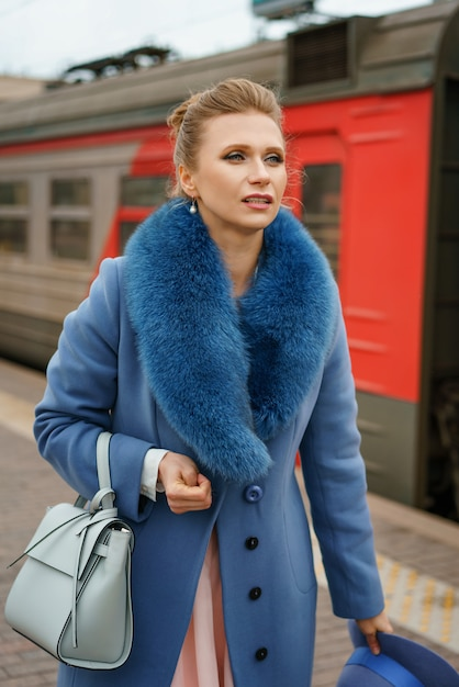 Glamorous woman standing on the platform of the railway station and waiting for the train Premium Photo