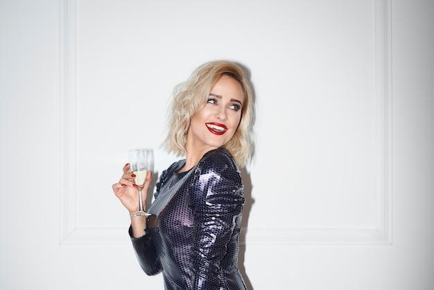 コピースペースを見ているシャンパンを持つ魅力的な女性 無料写真