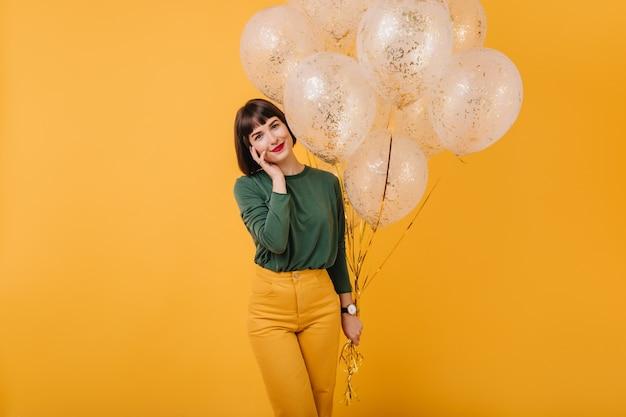 스파클 풍선의 무리와 함께 포즈 스트레이트 머리를 가진 매력적인 여자. 녹색 스웨터와 노란색 바지에 웃는 평온한 소녀의 실내 샷. 무료 사진