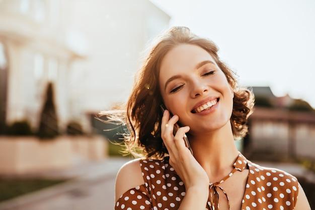 目を閉じて電話で話している魅力的な若い女性。短い茶色の髪のかわいい白人の女の子の屋外ショット。 無料写真