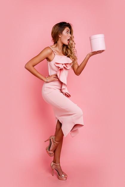 Гламурная блондинка с удивлением лицом, держа подарочной коробке и стоя над розовой стеной в элегантном розовом платье. восторженные эмоции. Бесплатные Фотографии