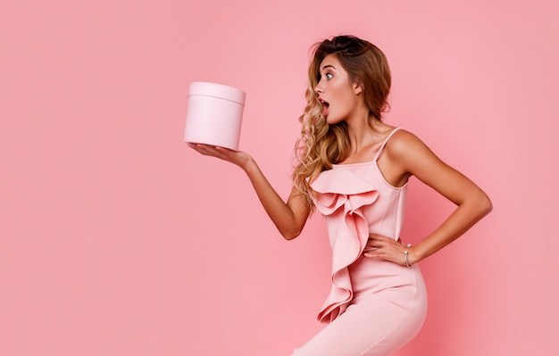Glamour blonde girl with surprise face holding gift box and standing over rose wall in elegant pink dress. ecstatic emotions. Free Photo