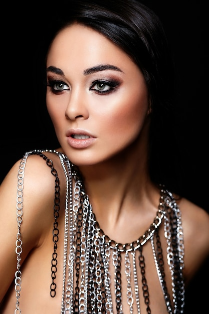 Glamour closeup portrait of beautiful young woman with juicy lips, bright black makeup and jewelry isolated on black Free Photo