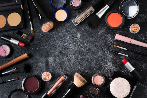 Glamour cosmetics scattered on dark dusty background Free Photo