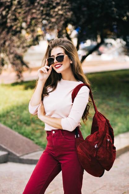Ragazza glamour con i capelli lunghi in occhiali da sole è in posa sulla strada. ha il colore del marsala sui vestiti e sembra apprezzata. Foto Gratuite