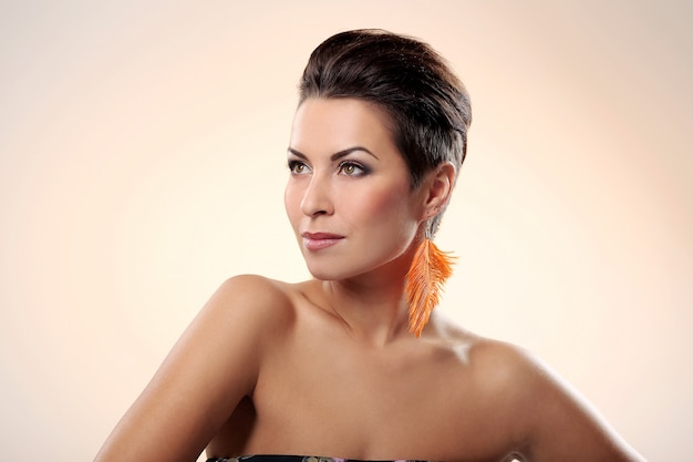 Glamour and gorgeous brunette with feather earring Free Photo