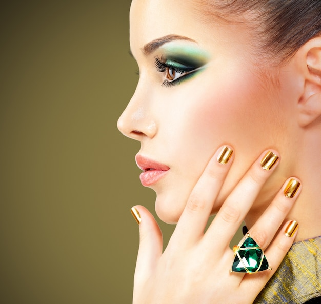 Glamour woman with beautiful golden nails and emerald ring on hands Free Photo