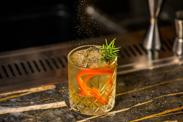 A glass of alcohol cocktail with rosemary leaves, ice cubes and orange spaghetti skin Free Photo