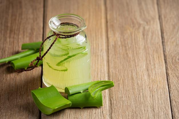 Bicchiere di succo di aloe vera messo sul pavimento di legno Foto Gratuite