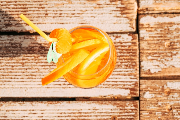 Glass of appetizing orange drink with lime on wooden surface Free Photo