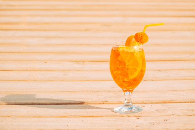 Glass of appetizing orange drink on wooden surface Free Photo