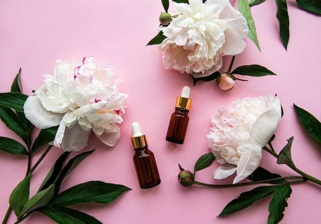 ピンクのパステルカラーのガラスのアロマオイルボトルと牡丹の花。 Premium写真