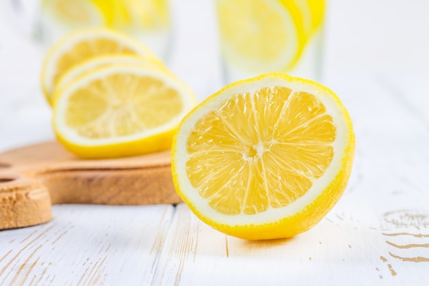 A glass beaker and a jug of cold lemonade on a white wooden background surrounded by lemons. Premium Photo