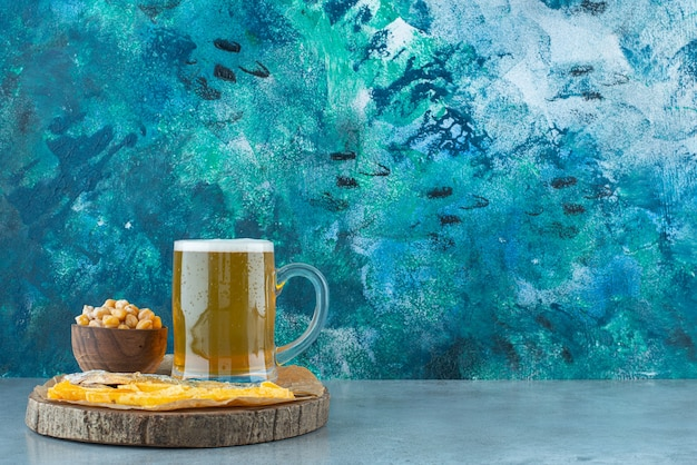 A glass of beer and appetizers on board on blue. Free Photo