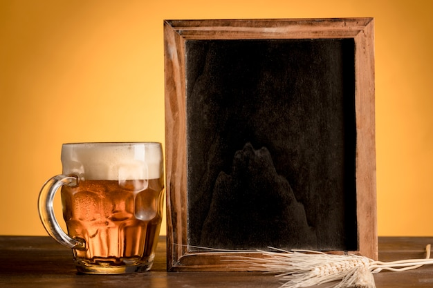 Glass of beer and blackboard on wooden table Free Photo
