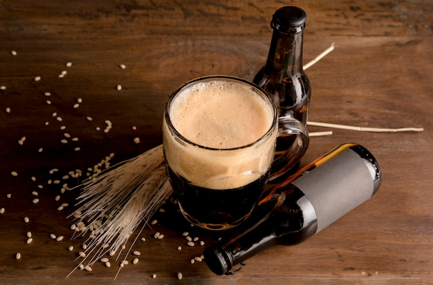 Glass of beer in foam with brown bottles of beer on wooden table Free Photo