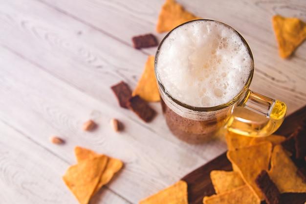 Стеклянная пивная кружка и пивные закуски на дереве, вид сверху Premium Фотографии