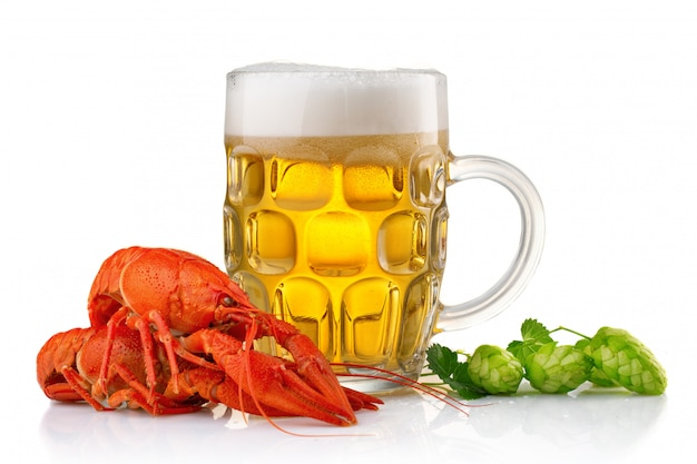 Glass of beer with boiled crayfishes and green hop Premium Photo