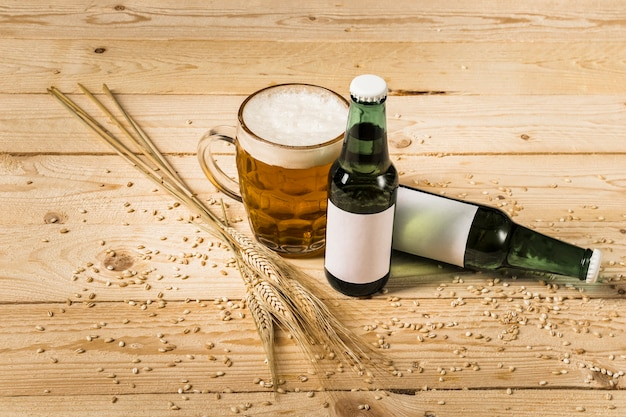 Glass of beer with bottles and ears of wheat on wooden plank Free Photo